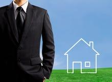 Mann, der ein Haus auf einem Gebiet zeichnet Stockbild