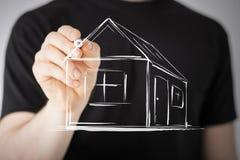 Mann, der ein Haus auf virtuellem Schirm zeichnet Lizenzfreie Stockbilder