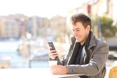 Mann, der ein intelligentes Telefon in einer Kaffeestube im Winter verwendet stockfotos
