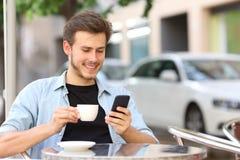 Mann, der ein intelligentes Telefon in einer Kaffeestube verwendet stockfotografie