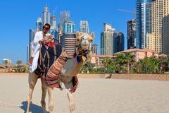 Mann, der ein Kamel auf den Strand reitet Lizenzfreie Stockfotografie