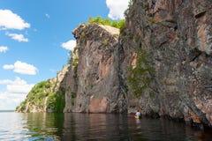 Mann, der ein Kanu entlang den Klippen schaufelt Stockbilder