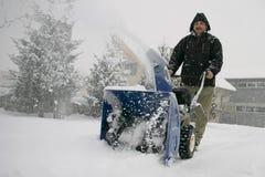 Mann, der ein leistungsfähiges Schneegebläse verwendet Lizenzfreie Stockfotografie