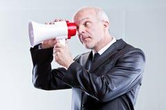 Mann, der ein Megaphon mit Augen anstelle des Munds verwendet Lizenzfreie Stockbilder