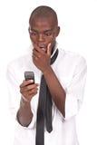Mann, der ein Mobiltelefon anhält und überrascht schaut Lizenzfreies Stockbild
