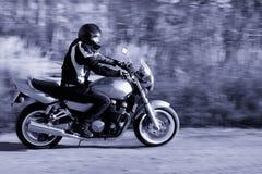 Mann, der ein Motorrad auf die Straße reitet Stockfoto