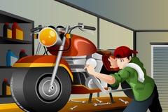Mann, der ein Motorrad repariert Stockbild