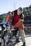 Mann, der ein Motorrad streichelt Stockbild