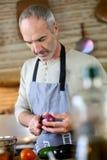 Mann, der ein oignon in der Küche schneidet Lizenzfreie Stockfotografie
