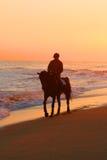 Mann, der ein Pferd auf Strand reitet Lizenzfreie Stockbilder