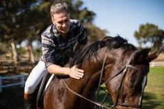 Mann, der ein Pferd in der Ranch reitet stockbild