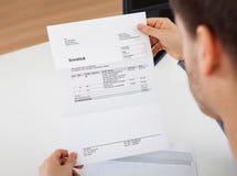 Mann, der ein Rechnungsdokument liest Stockfoto