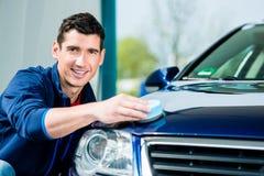 Mann, der ein saugfähiges Tuch für das Trocknen der Oberfläche eines Autos verwendet Stockfotografie