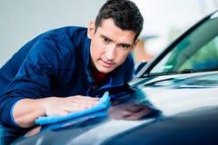 Mann, der ein saugfähiges Tuch für das Trocknen der Oberfläche eines Autos verwendet Lizenzfreie Stockbilder