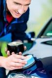 Mann, der ein saugfähiges Tuch für das Trocknen der Oberfläche eines Autos verwendet Stockbild