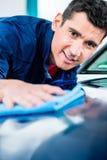 Mann, der ein saugfähiges Tuch für das Trocknen der Oberfläche eines Autos verwendet Stockfoto