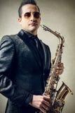 Mann, der ein Saxophon hält Stockfoto