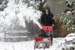 Mann, der ein Schnee-Gebläse verwendet Lizenzfreie Stockfotos