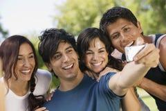 Mann, der ein Selbstporträt mit seinen Freunden nimmt Stockbild