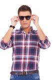 Mann, der ein Sonnenbrillen setzt Stockfoto