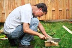 Mann, der ein Stück Holz sägt Lizenzfreies Stockbild
