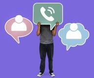 Mann, der ein Telefonsymbol für Telekommunikation hält lizenzfreie stockfotografie