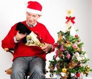 Mann, der ein Weihnachtsgeschenk auspackt Lizenzfreie Stockfotos