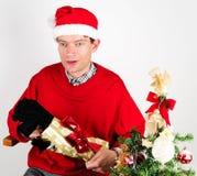 Mann, der ein Weihnachtsgeschenk auspackt Stockbild