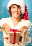 Mann, der ein Weihnachtsgeschenk hält lizenzfreie stockbilder