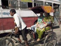 Mann, der eine alte Rikscha fährt. Stockbilder