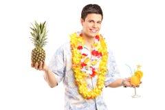 Mann, der eine Ananas und ein Cocktail hält Stockfoto