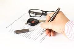 Mann, der eine Autokaufform unterzeichnet Lizenzfreie Stockbilder