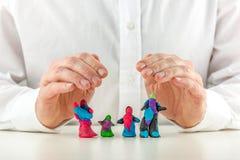 Mann, der eine bunte Plasticinefamilie schützt Stockbild
