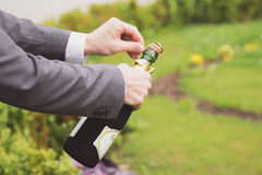 Mann, der eine Champagnerflasche öffnet Stockbild