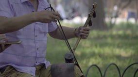 Mann, der eine chinesische zwei aufgereihte Geige spielt stock video footage
