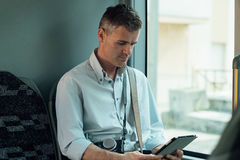 Mann, der eine digitale Tablette auf einem Bus verwendet Lizenzfreies Stockfoto