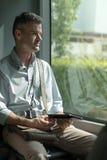 Mann, der eine digitale Tablette auf einem Bus verwendet Lizenzfreies Stockbild
