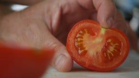 Mann, der eine frische Tomate in den Scheiben schneidet lizenzfreies stockbild