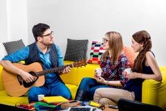 Mann, der eine Gitarre mit Freundinnen spielt Stockfotos