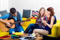 Mann, der eine Gitarre mit Freundinnen spielt Stockfotografie