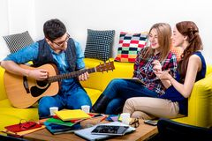 Mann, der eine Gitarre mit Freundinnen spielt Lizenzfreies Stockbild