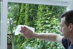 Mann, der eine gleitendes Glas-Tür säubert Stockfotografie