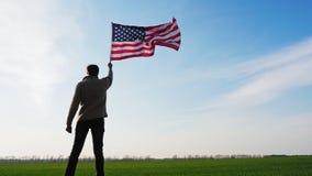 Mann, der eine große Flagge der Vereinigten Staaten von Amerika hält stock video footage