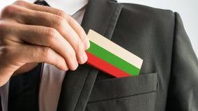 Mann, der eine hölzerne Karte gemalt als die bulgarische Flagge zurücknimmt Stockbild