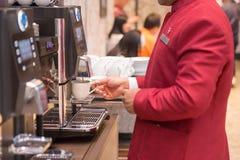 Mann, der eine Kaffeemaschine verwendet stockfotografie