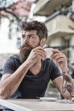 Mann, der eine Kaffeepause nimmt Bärtiger Mann hält Espressoschale, trinkt Kaffee an der Terrasse Mann mit langem Bart schaut trä Stockbild