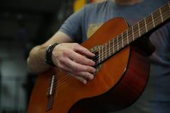 Mann, der eine klassische Gitarre spielt Hand hebt die Schnüre auf der Gitarre auf stockfotografie