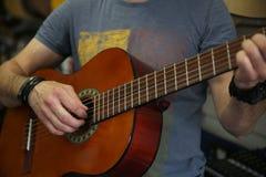 Mann, der eine klassische Gitarre spielt Hand hebt die Schn?re auf der Gitarre auf stockbild