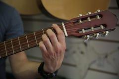 Mann, der eine klassische Gitarre spielt Hand hebt die Schn?re auf der Gitarre auf stockfoto