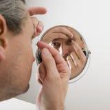 Mann, der eine Kontaktlinse einsteckt Stockbilder